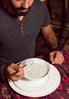 Мужчина ест довга, яйлу, кавказский суп из йогурта