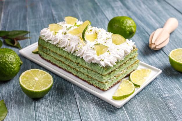 Вкусный лаймовый торт со свежими лаймовыми ломтиками и лаймами.