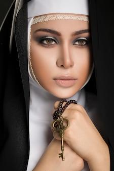 彼の手でキーを保持したヒジャーブの黒い服を着た若いイスラム教徒の女性を閉じる