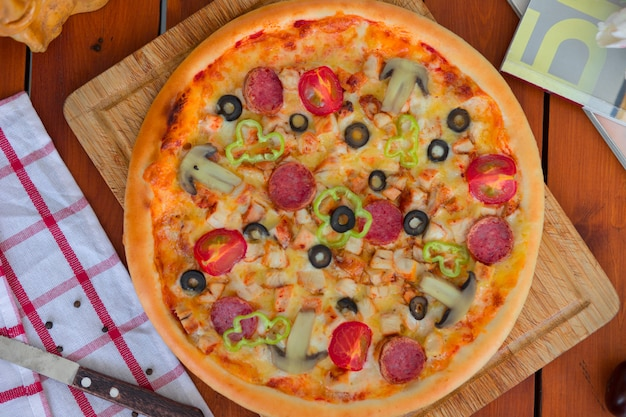 Пицца пепперони с болгарским перцем, ломтиками томатов, грибами и оливками.