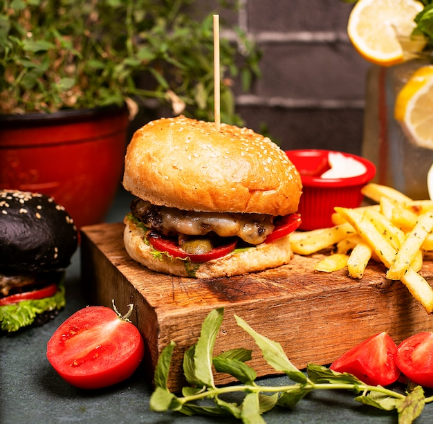 野菜のファーストフード、フライドポテトとケチャップとビーフチーズバーガー
