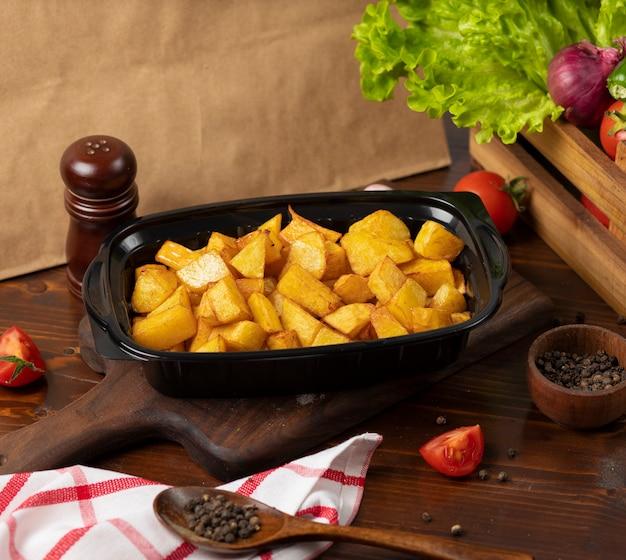 Жареный картофель с выносом трав в черном контейнере.