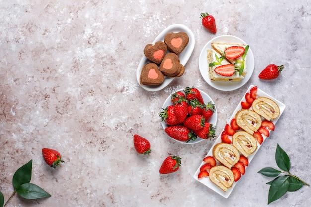 Вкусный клубничный рулет, печенье в форме сердца, кусочки торта со свежей клубникой, вид сверху