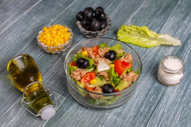 Салат из тунца с листьями салата, маслинами, кукурузой, помидорами, вид сверху
