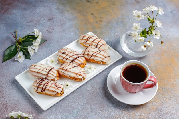 Эклеры или профитроли с черным шоколадом и белым шоколадом с заварным кремом внутри, традиционный французский десерт.