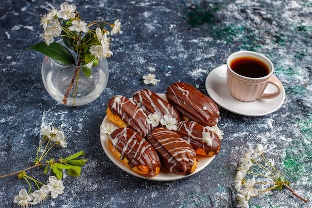 エクレアまたはプロフィットロール、ブラックチョコレート、ホワイトチョコレート、内部にカスタード、伝統的なフランスのデザート。