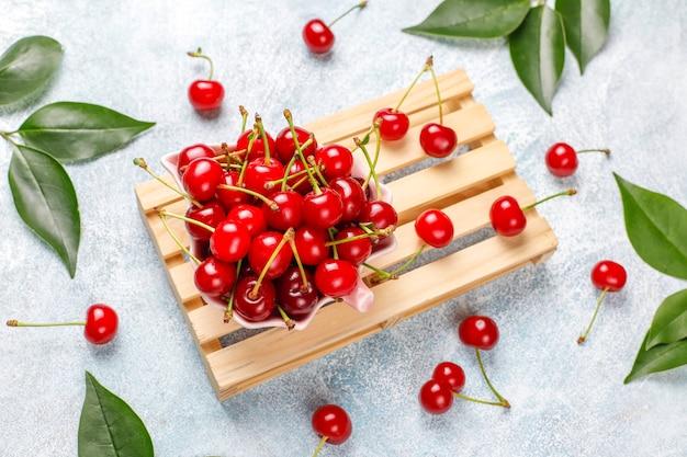 Красная вишня в тарелку на сером столе