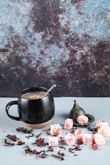 一杯のコーヒーと金属の受け皿にトルコの喜びロクム