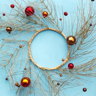 クリスマスまたは新年の冬の組成。黄金の木の枝とクリスマスの装飾品で作られたラウンドフレーム。