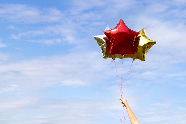 空の雲にカラフルな黄金の光沢のある星形の風船
