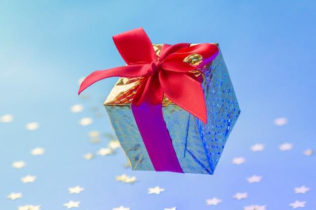 Золотая подарочная коробка с красной лентой, плавающей на синем фоне с блестящими звездами