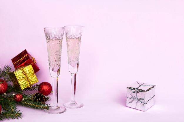Новогодняя зимняя композиция с двумя бокалами шампанского на розовом фоне