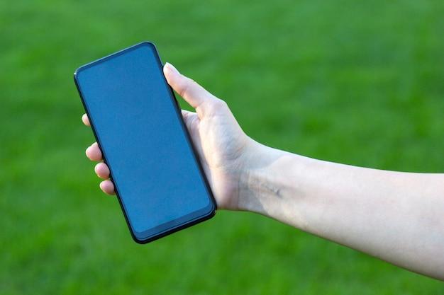 空白の画面を持つ現代のスマートフォンを持つ女性の手。