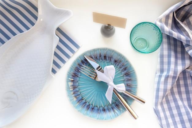 Столовый сервиз в морском стиле - пустые тарелки в форме рыбы, стакан, вилка и нож на полосатых салфетках, вид сверху