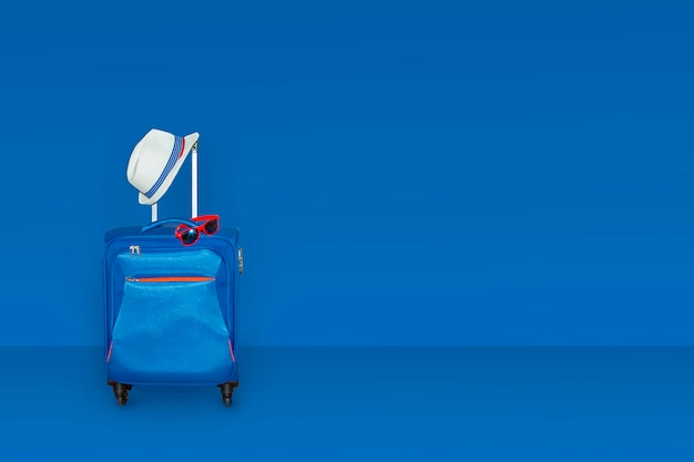 夏の帽子とクラシックな青い色の壁の調子を整えるサングラスのスーツケース。