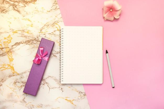 Набор женских аксессуаров письменный - блокнот с ручкой, розовая коробка подарков, цветок, вид сверху