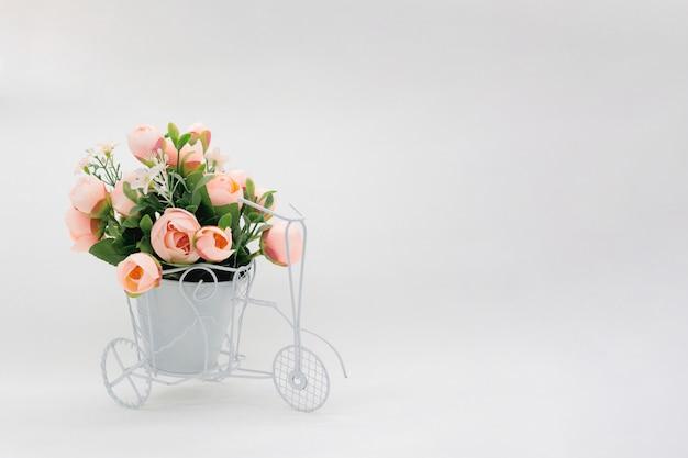 明るい背景に花のポットとレトロな自転車。
