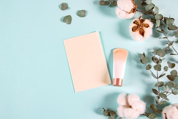 ユーカリの葉、クリームの瓶、明るい背景に綿の花を持つ空白の紙封筒
