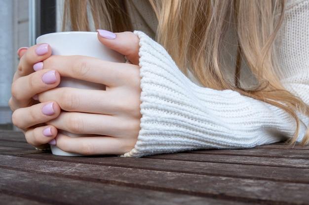 木製のテーブルにコーヒーや紅茶のマグカップを保持している女性の手。