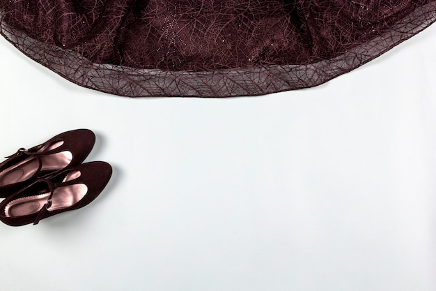 Черное платье для коктейля, обувь на светлом фоне.