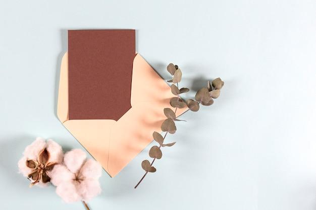 空白のクラフト紙の封筒、ユーカリの葉と光の綿の花とメール