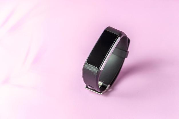 Активный умный трекер на светло-розовой стене, спортивный браслет