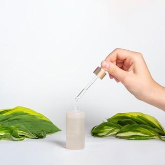 Пипетка-капельница с каплей натурального масла над стеклянной бутылкой на поверхности с зелеными листьями