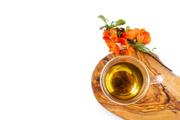開花マルメロリンゴの木の枝と熱い緑茶のガラスのコップ