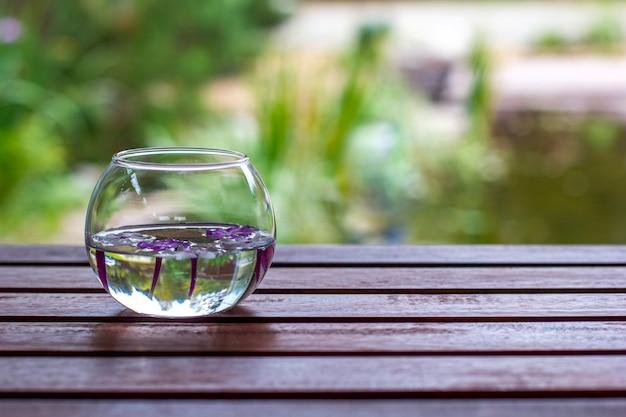 ぼかしの背景を持つ木製のテーブルの上に浮かぶ花と丸いガラス花瓶