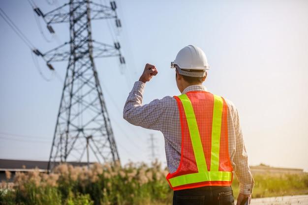 白いヘルメットを持つ技術者は、高電圧発電所を検査します