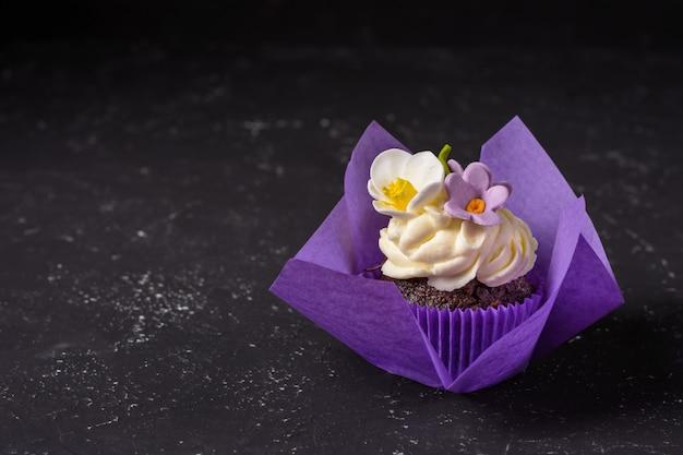 暗い石のテーブルの上に紫色のラップでカップケーキ。最小限の概念スペースをコピーします。