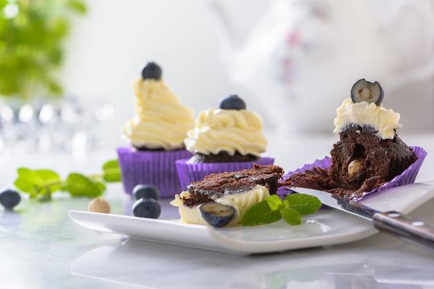 大理石のテーブルの上に紫色のラップでブルーベリーとヘーゼルナッツの白いプレートにカップケーキをカットします。