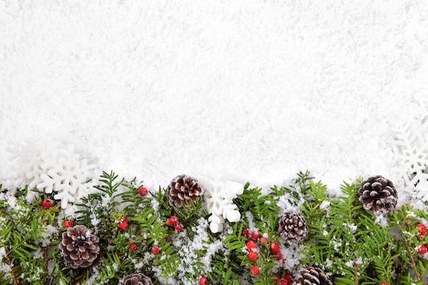 雪の上の松ぼっくりとクリスマスの飾り