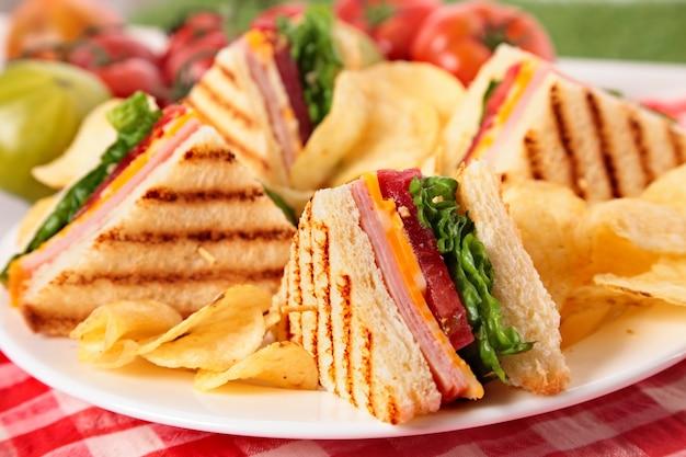 ピクニックテーブルにハムとチーズクラブサンドイッチ