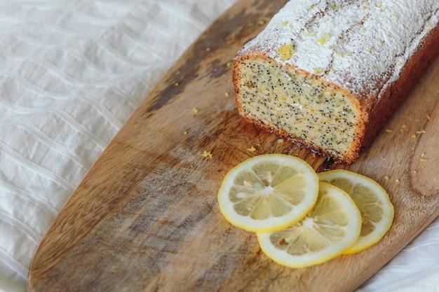 ケシの実とレモンの皮、粉砂糖をまぶしたケーキ。木の板にレモンのカップケーキ。