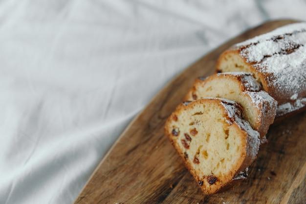 Пирог с изюмом, посыпанный сахарной пудрой. кекс с изюмом на деревянной доске.