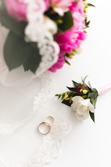 美しいピンクの牡丹の花束と結婚指輪は白いテーブルにあります。