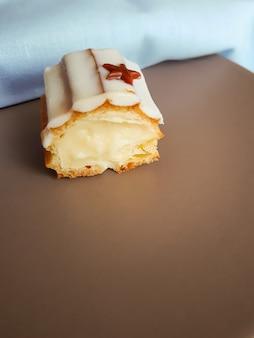 Срез эклера с ванильным кремом, покрытый белой шоколадной глазурью на коричневой тарелке.