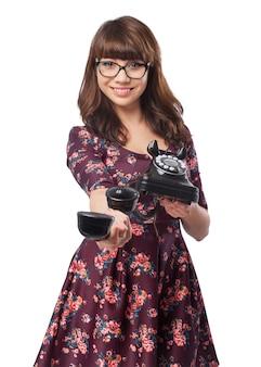 Положительная молодая женщина с помощью ретро телефон