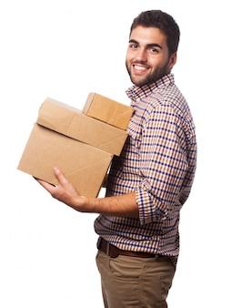Человек взимается с ящиками и улыбается