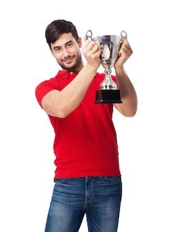 Гордый подросток держит серебряный кубок