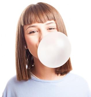 Подросток делает пузырь с жевательной резинки