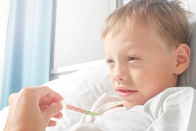 母親が体温を取っている間に、男の子は体温でベッドで病気になります。子供は風邪をひいた。ヘルスケア、インフルエンザ、衛生。