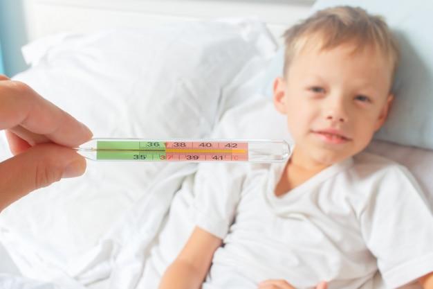 回復期。水銀温度計は、赤ちゃんの通常の体温を示します。風邪やインフルエンザから回復する少年。