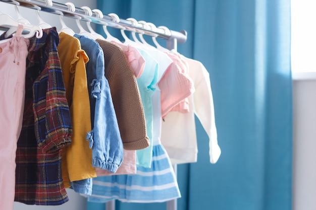 子供用クロスラック、セレクティブフォーカス。屋内のオープンハンガーに並んでいるパステルカラーの子供服。