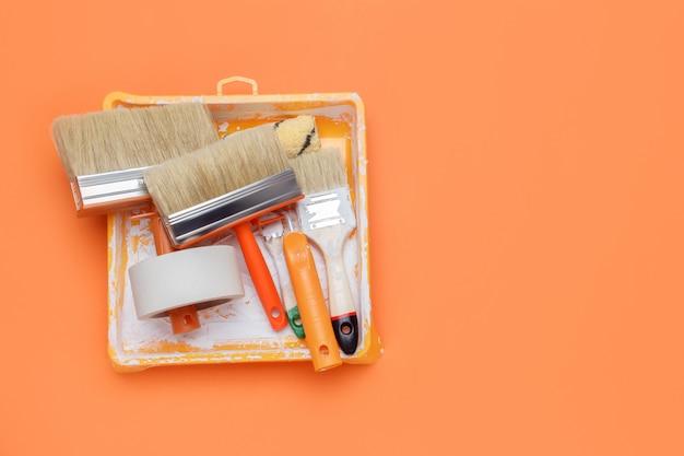 ペイントツールのセット:ペイントブラシ、マスキングテープ、オレンジ色の背景のペイントローラー。