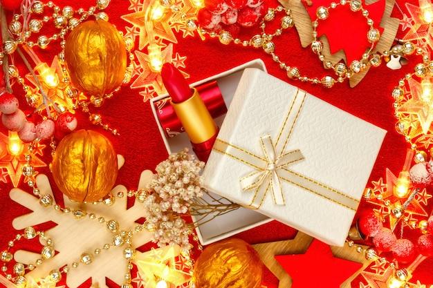 女性の赤い口紅。金色の光沢のあるお祝いのギフトボックスに化粧品。新年、クリスマスプレゼント。