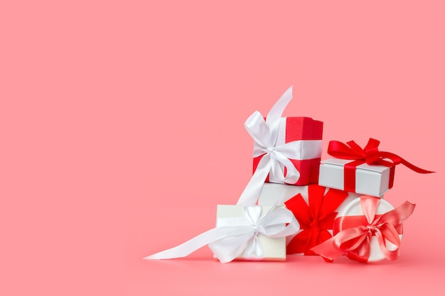 ピンクの背景に赤いサテンのリボンと白いギフトボックス。聖バレンタインの日、国際女性の日、結婚式、婚約のお祝いプレゼント。