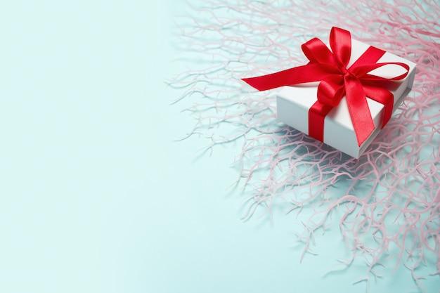 あなたの愛する人に海での休暇を与えます。サンゴの枝に赤いサテンの弓のギフトボックス。ギフトとプレゼント。休日と休暇。夏の計画。