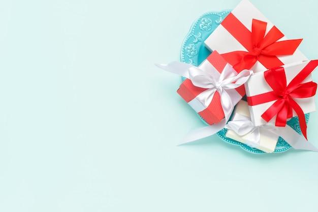バレンタイン・デー。パステルブルーの背景に楕円形の皿のギフト。バレンタインデーのコンセプト。コピースペース。
